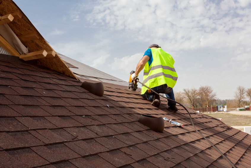 Construction worker putting the asphalt roofing (shingles) with nail gun on a large commercial apartment building development