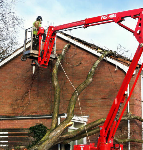 Tree surgeon working up cherry picker repairing storm damaged roof after an uprooted tree fell on top of a residential house
