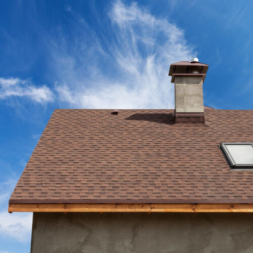 New roof with skylight, asphalt roofing (shingles) and chimney. Roof with mansard windows.